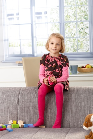 little girl smiling: Little girl sitting on sofas back-rest at home, smiling, looking away.