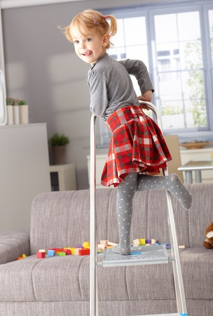 misbehaving: Cute 3 year old little girl posing on ladder in living room, sticking tongue.