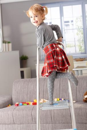 maliziosa: Cute bambina di 3 anni poco in posa sulla scala in soggiorno, linguaccia. Archivio Fotografico