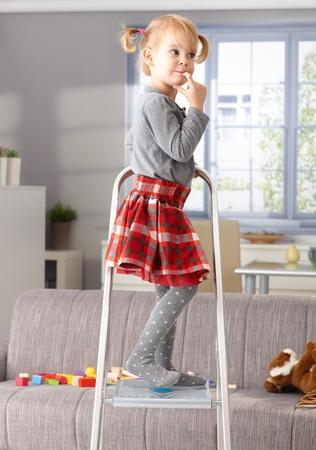 Elfish little girl standing on top of ladder, thinking impishly.