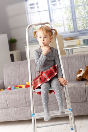 the color of silence: Cute little girl sitting impishly on ladder, putting forefinger on lips as calling for silence. Stock Photo