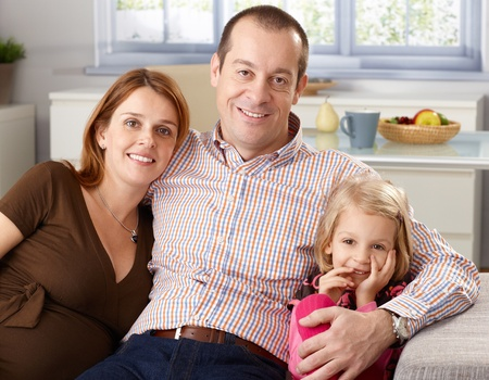 Portrait of happy family at home, father hugging little daughter and pregnant wife, all smiling. photo