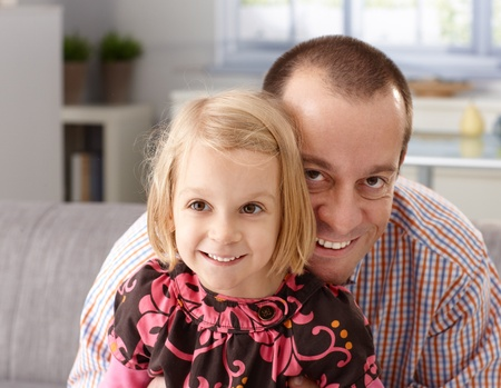 Portrait of happy father and little daughter embracing heads together, laughing, having fun. Stock Photo - 13138385