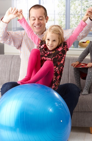Father and little daughter playing with fit ball in living room, having fun, smiling. photo