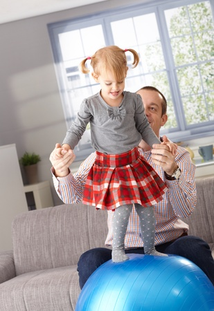 Little girl balancing on fit ball at home in living room, father helping by holding hands. photo
