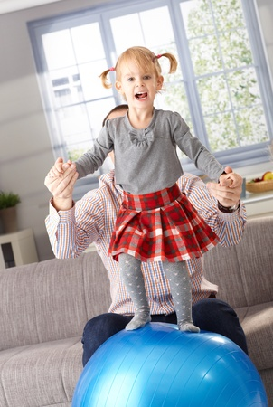 Happy little 3 year old girl standing on fit ball, father helping from background. photo