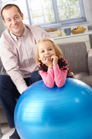 Little girl leaning on fit ball smiling, father watching from background. photo