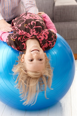 Little girl laying upside down on fit ball, laughing, father holding hands from background. photo