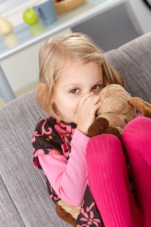 Little girl sitting on sofa at home, sucking thumb, hugging soft toy, smiling. photo