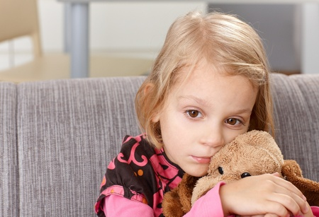 sad child: Lonely little girl sitting sadly on sofa at home, hugging plush toy. Stock Photo