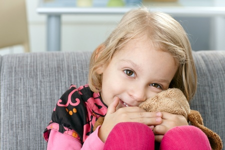 Cute little girl smiling impishly on sofa, hugging soft toy. photo