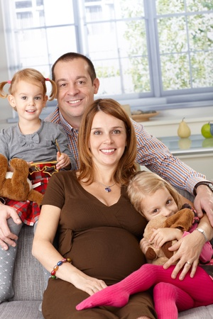 Portrait of happy family at home with father, pregnant mother and two daughters. photo