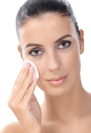Closeup portrait of young attractive woman removing makeup by cotton pad. photo