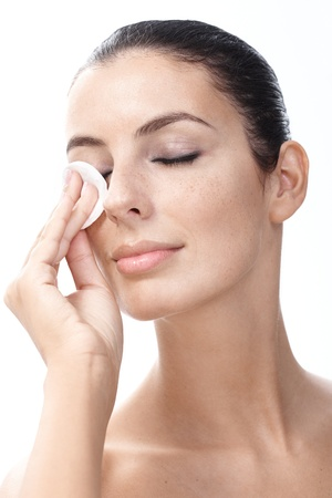 removing: Young woman removing eye makeup by cotton pad eyes closed.