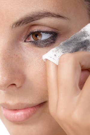 Closeup portrait of young woman removing eye makeup, by cotton pad.