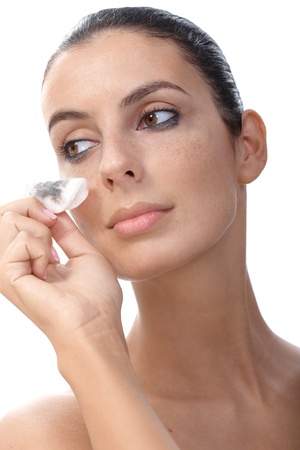 removing make up: Young woman wiping away eye makeup by cotton pad. Stock Photo