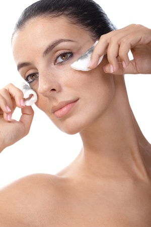 Young female removing eye makeup by cotton pads. Stock Photo - 13180331