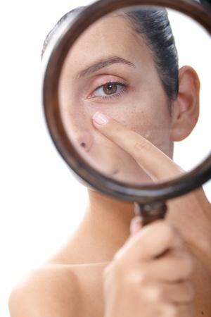 Junge Frau untersucht ihre Haut durch Lupe, auf der Suche nach Mitessern.