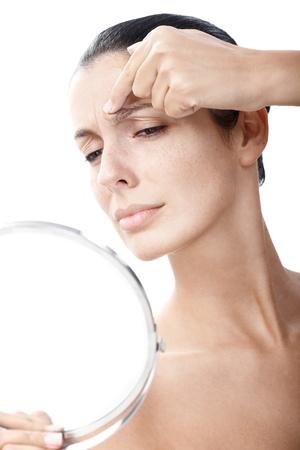 arrugas: Mujer joven que mira a s� misma en el espejo, examinar las arrugas en la frente.