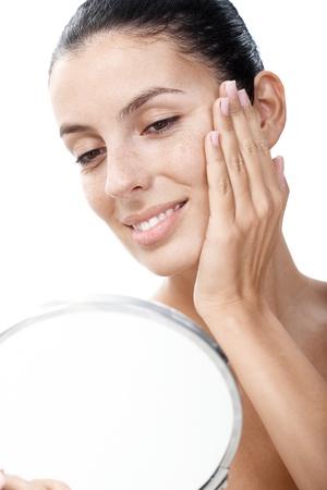 spiegelbeeld: Jonge lachende vrouw op zoek naar haar gezicht in de spiegel tevreden.
