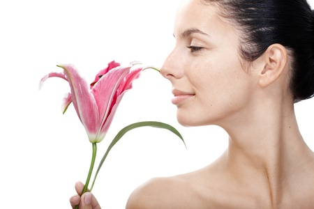 Young female smelling lily, profile, bare shoulders.