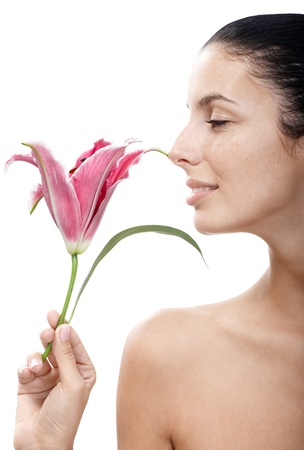 Young attractive woman profile smelling lily, bare shoulders.