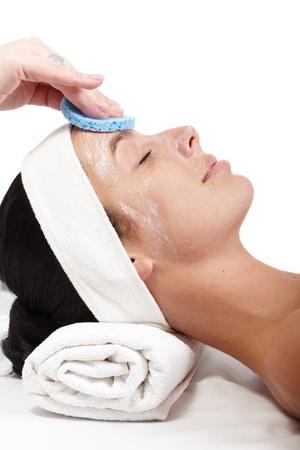 pulizia viso: Estetista la rimozione della maschera facciale dal viso di donna, vista laterale.