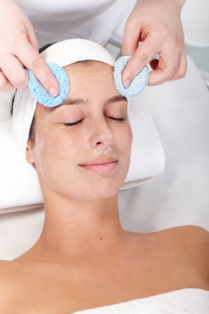 beauty parlour: Beautician removing facial cream by sponge from females face. Stock Photo