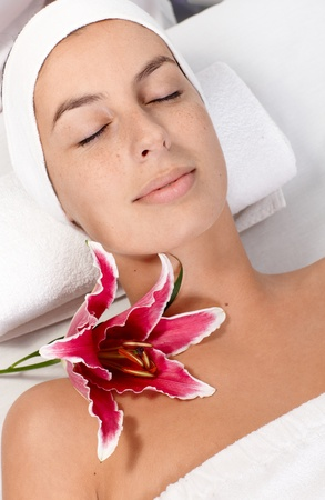 Young woman laying eyes closed in dayspa, getting facial treatment, relaxing. Stock Photo - 13180328