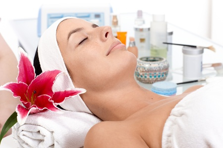 parlour: Young female relaxing eyes closed in beauty parlour, receiving treatment.