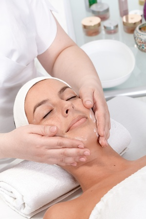 beauty saloon: Young woman receiving facial massage in dayspa, relaxing eyes closed.