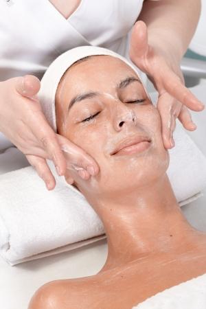 tratamiento facial: Mujer joven recibiendo masaje facial en esteticista.