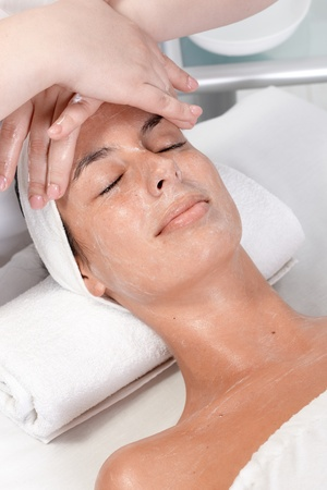 Young woman receiving face massage in dayspa, laying relaxed eyes closed. photo
