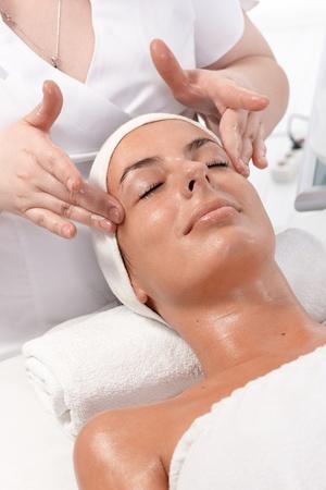 gezichtsbehandeling: Facial schoonheidsbehandeling, tot massage in dayspa, jonge vrouw ontspannen. Stockfoto