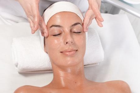 masajes faciales: Joven mujer recibiendo masaje facial en el salón de belleza, sobre normas relajado.