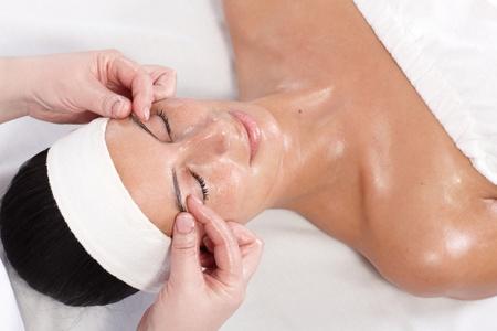 gezichtsbehandeling: Jonge vrouwelijke krijgt gezicht schoonheid massage in dayspa, bekijken van boven.