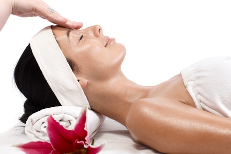 Young woman receiving facial massage, beauty treatment, side view. photo