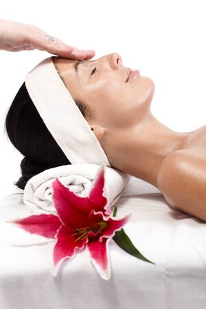 Closeup portrait of young woman receiving facial massage, laying eyes closed, side view. photo