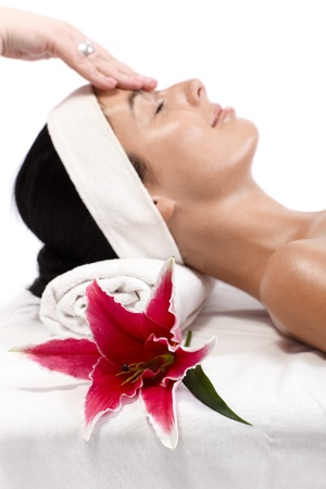 Closeup portrait of young woman getting facial massage with lily in foreground photo