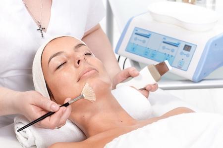 facial massage: Jeune femme portant d�tendu, recevant un traitement facial � esth�ticienne.