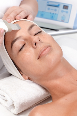 beauty saloon: Closeup portrait of young woman receiving facial beauty treatment. Stock Photo
