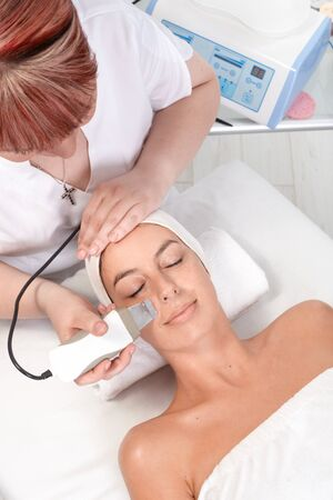 beauty saloon: Young woman getting skin rejuvenating treatment at beautician, view from above.