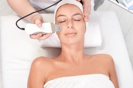 facial massage: Jeune femme pose les yeux ferm�s, se faire soigner la beaut� du visage, vue de dessus. Banque d'images