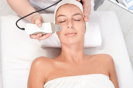 beauty saloon: Young woman laying eyes closed, getting facial beauty treatment, view from above. Stock Photo