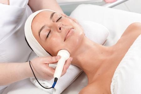 ansikts: Ung kvinna om slutna ögon, som får ansiktsbehandling skönhetsbehandling i skönhetssalong.