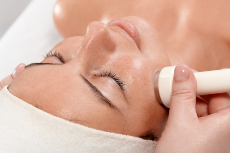 Closeup portrait of young woman receiving facial beauty treatment, laying eyes closed. Stock Photo