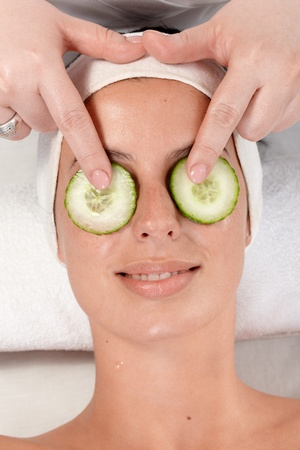 parlour: Closeup portrait of young woman with natural beauty treatment with cucumber on both eyes. Stock Photo