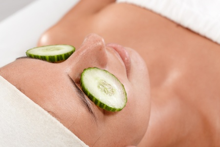 parlour: Closeup portrait of young woman with natural facial beauty treatment, cucumber on eyes. Stock Photo