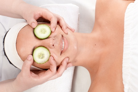Young woman receiving natural facial treatment with cucumber. photo