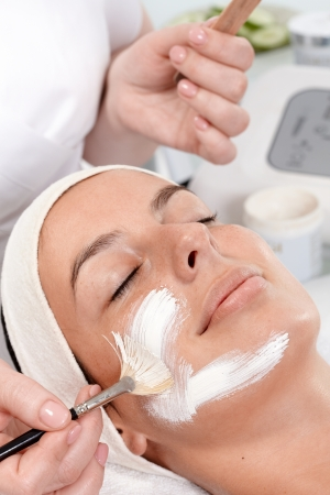 dayspa: Beautician applying facial cream on womans face, woman laying eyes closed with headband. Stock Photo